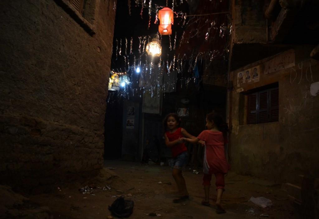 أطفال يلعبون فى إحدى الحوارى بعد تعليق زينة رمضان