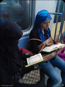 سيدتان يقرأن القرآن اثناء رحلتهم بمترو القاهرة فى نهار رمضان
